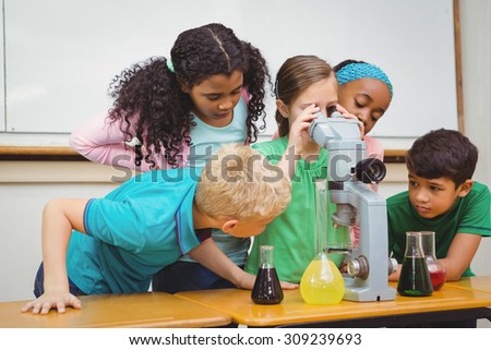 Students using science beakers and a microscope at the elementary school #309239693