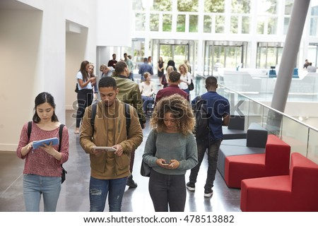 Students walk in university campus using tablets and phone
