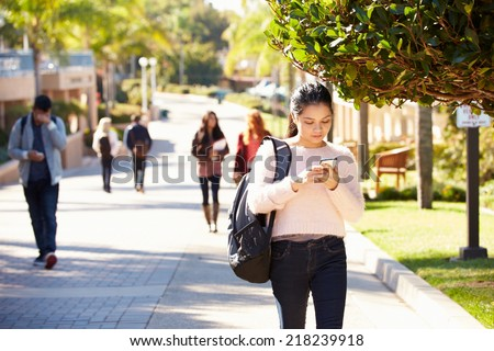 Students Walking Outdoors On University Campus - stock photo