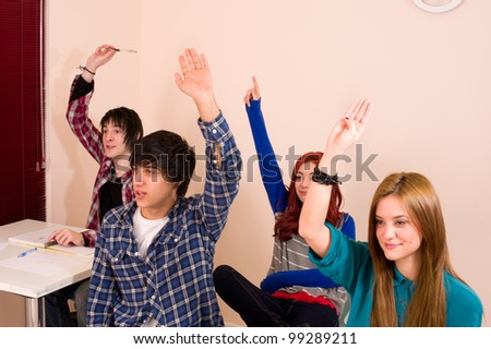 Students with hands raised, a motivated group