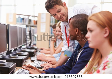 Students Working At Computers In Library With Teacher