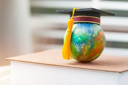 Studies at Home when covid-19,coronavirus outbreak disease 2019 concept, Education to learn study in world while Pandemic. Graduated student studying abroad international Master degree hat on globe