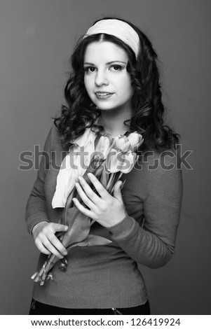 Studio black and white image of beautiful young woman with fresh tender tulips/European young girl with a bouquet of spring flowers