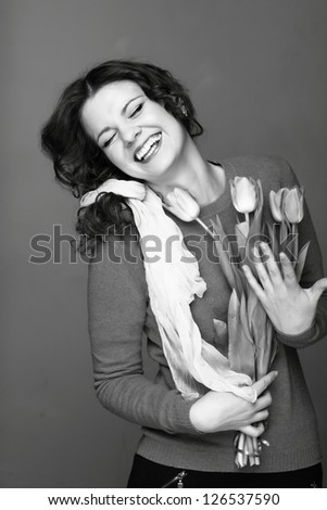 Studio black and white image of beautiful young woman with fresh tender tulips/Smiley young girl with a bouquet of spring flowers