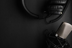 Studio black studio microphone with studio headphones on a black background. Banner. Radio, work with sound, podcasts.