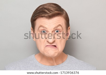 Studio close-up portrait of blond mature man with angry annoyed expression on face, grimacing from rage, looking straight ahead. Headshot over gray background Сток-фото ©