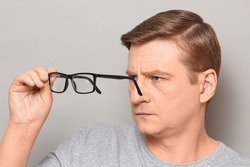 Studio close-up portrait of serious blond mature man peering through his glasses at something interesting with concentrated expression on face and attentively. Headshot over gray background