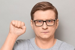 Studio close-up portrait of serious blond mature man with glasses, raising fist up, looking rebellious and confident, protesting, being ready to protect his rights. Headshot over gray background