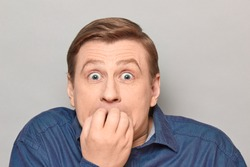 Studio close-up portrait of shocked frightened blond mature man wearing shirt, panicking and biting nails, with eyes widened and full of fear, looking straight ahead. Headshot over gray background
