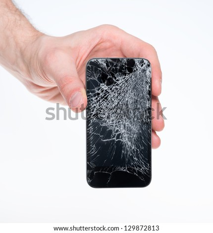 Studio closeup of a male hand, holding a smartphone with cracked screen, isolated on  white background.