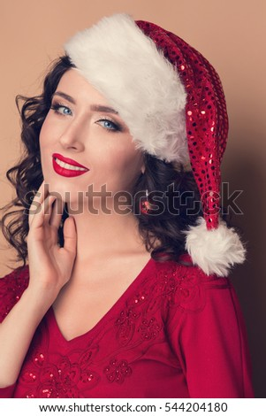 b49f813f9f782 Studio closeup portrait of a beautiful girl with a red lipstick in the hat  of Santa