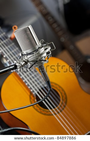 Studio condenser mic in the foreground with an acoustic guitar blurred out in the background