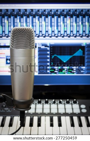 studio condenser microphone, midi keyboard synthesizer & digital mixer on screen monitor for computer music or broadcasting concept background