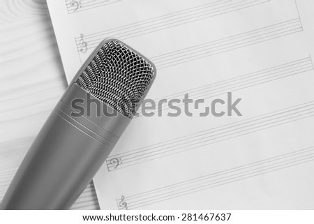 studio condenser microphone on blank music sheet, on wood / black and white processed for music concept background