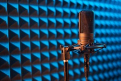 Studio condenser microphone on blue acoustic foam panel background with copy space on left