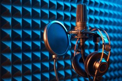 Studio condenser microphone with professional headphones and pop-up filter on blue acoustic foam panel background