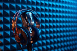 Studio condenser microphone with professional headphones on acoustic foam panel background with blue and orange light, copy space on right