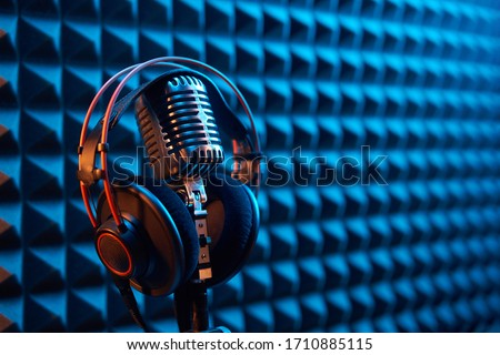 Studio condenser microphone with professional headphones on acoustic foam panel background with blue and orange light, copy space on right ストックフォト ©