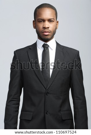 Studio fashion portrait of a handsome young African American businessman wearing a black suit and tie. Isolated on gray background Stock photo ©