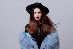 Studio fashion portrait of gorgeous  woman in stylish winter fluffy  blue coat and black hat posing on bright  grey background.
