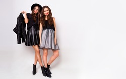 Studio fashion portrait of two elegant young women in fall stylish outfit posing in studio. Fashionable girls in skirts, bright make up, monochrome  clothes. Dress collection.