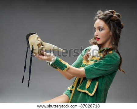 studio fashion portrait of young woman in vintage outfit, posing with venetian mask