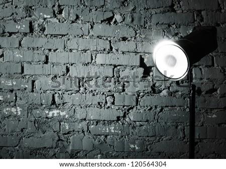 Studio flash near the gray damaged brick wall