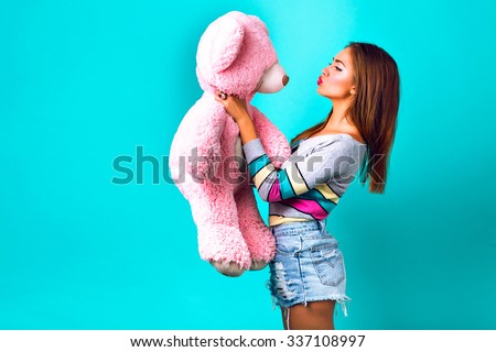 Studio funny portrait of pretty  woman playing with big fluffy teddy bear, mint background, sweet pastel colors. holding her present and sending kiss, making funny face, holidays, joy, childhood.