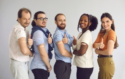 Studio group portrait of happy healthy responsible multiethnic male and female citizens giving thumbs-up after receiving vaccine. Diverse people promoting vaccination during World Immunization Week
