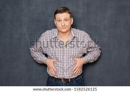 Studio half-length portrait of dissatisfied man having overweight caused by metabolic disorder or overeating, putting hands on his fat stomach, looking disappointed and upset, over gray background