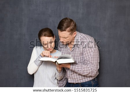 Studio half-length portrait of focused man and woman, reading with serious expression something interesting in book, over gray background. Concept of together gaining of knowledge and self-education