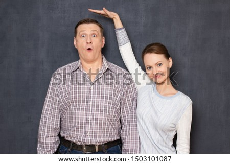 Studio half-length shot of happy short woman pulling up and showing with hand at height of surprised tall man standing beside her with eyes widened, over gray background. Variety of person's heights