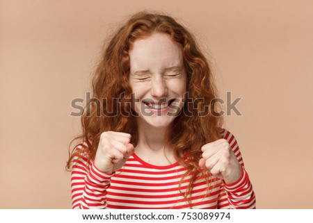 Studio headshot of young beautiful European woman with red curly hair isolated on peach background clenching fists and blinking as if supporting someone fiercely, looking enthusiastic and involved