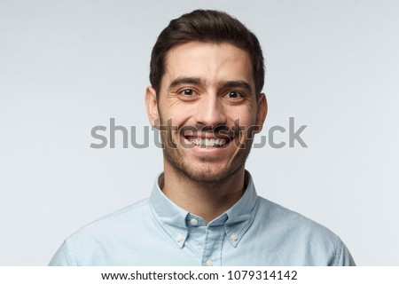Studio headshot of young happy European Caucasian man pictured isolated on gray background with short dark hair and formal light blue shirt, laughing positively and friendly showing pleasure