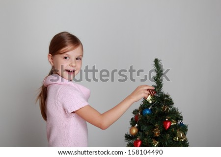 Studio image of a beautiful smiling little girl in a pink dress decorated Christmas tree in the New Year/Child near a decorated Christmas tree