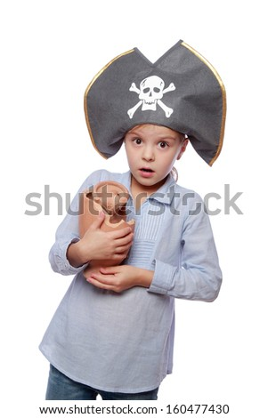 Studio image of a charming emotional little girl with a sweet smile as evil pirate in a pirate hat isolated on white on Holiday