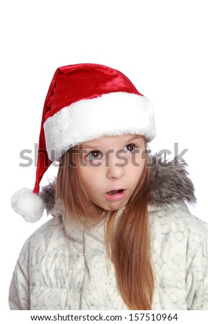Studio image of a surprised little girl in Santa's hat looking up isolated on white #157510964