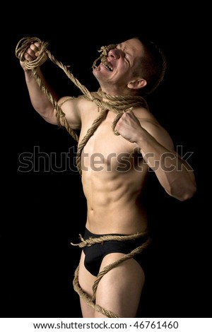 Studio image of a young man tied with ropes.