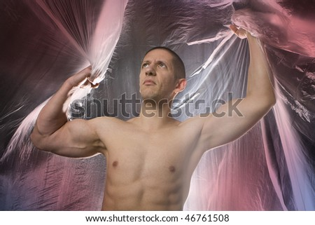 Studio image of a young muscular man on abstract colored background