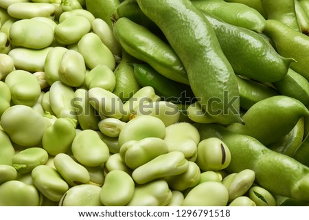 Studio image of both broad bean pods and shelled seeds.