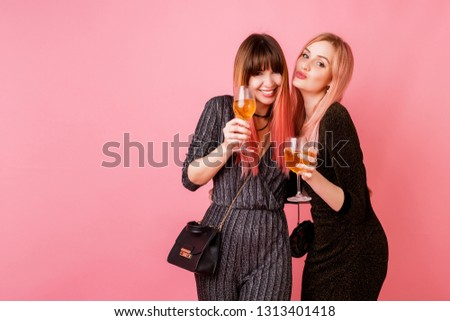 Studio image of celebrating women in party dress drinking shampagne and have great time together. Pink background. Happy emotions.