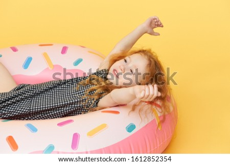 Studio image of cute funny little girl in dress chilling, lying in inflatable pink swimming circle raising hands and smiling happily, having carefree joyful facial expression. Happiness and joy