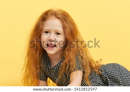 Studio image of cute joyful female child with loose ginger hair having excited amazed facial expression, being in good mood, posing isolated. Children, joy, relaxation and happiness concept