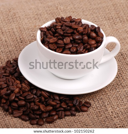 Studio image of dark brown roasted over light brown canvas background on Food and Drink theme/natural coffee beans