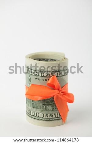 Studio image of dollars with orange ribbon over light gray background