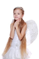 Studio image of lovely angelic little girl praying to the God on Christmas holiday isolated on white background/Pretty caucasian little angel looking up and praying gratefully