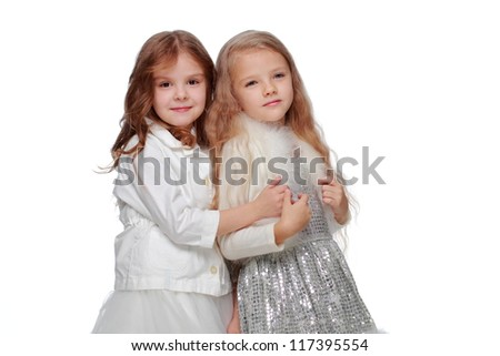 Studio image of two beautiful little girl in adorable white dresses isolated on white background/Joyful kids as Christmas princesses