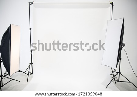 Studio is empty of the photographer with professional lighting arrangements. Flash, light equipment and white background scenes prepared for shooting in the studio. Modern photographer studio.