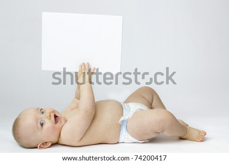 Studio Isolation of an Infant Child. The baby boy is Isolated on white with a Horizontal composition. He is laid on his back smiling into the camera whilst holding a white board in the air. - stock photo
