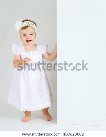 Studio Isolation of an Infant Child. The baby girl is Isolated on white with a Horizontal composition. She is holding a white board with copy space for text and has a huge surprised smiling expression